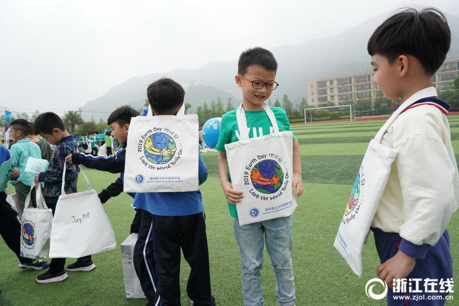 学生们在健康九州网赶牛阿旗布袋上绘画地球