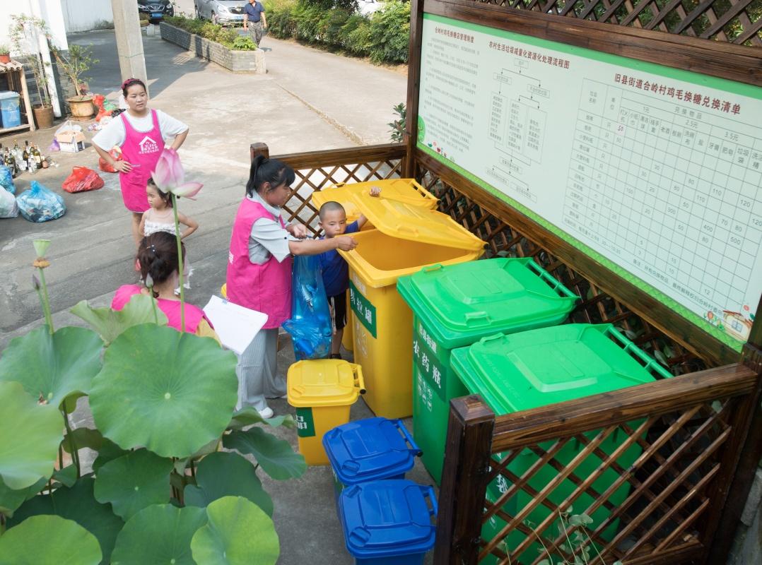"""6月10日,志愿者在旧县街道合岭村""""鸡毛换糖""""垃圾回收点进行垃圾分类投放。新华社记者 翁忻旸 摄"""