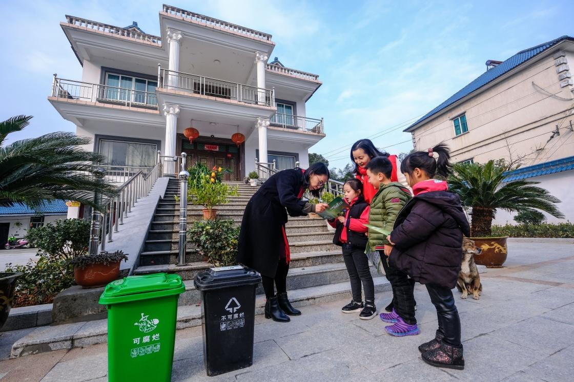 浙江长兴县李家巷中心幼儿园的孩子和老师向村民(左一)普及垃圾分类知识。 新华社记者 徐昱摄.jpg