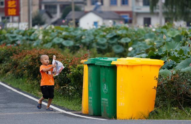 在浙江省安吉县港口村,一名儿童准备将垃圾扔进摆放在村口的分类垃圾桶。.jpg