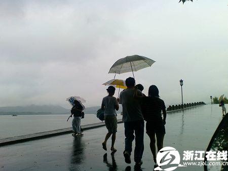 一家人打伞雨中游西湖