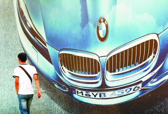 图为路人从南京街头宝马大幅广告牌前经过(2010年10月17日摄).图片