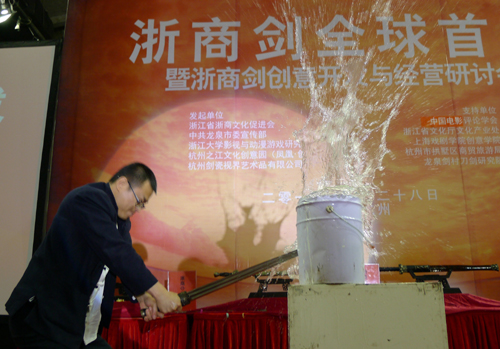 在浙商剑全球首发仪式上,一名铸剑师用一款浙商剑劈开一只铁皮水桶。