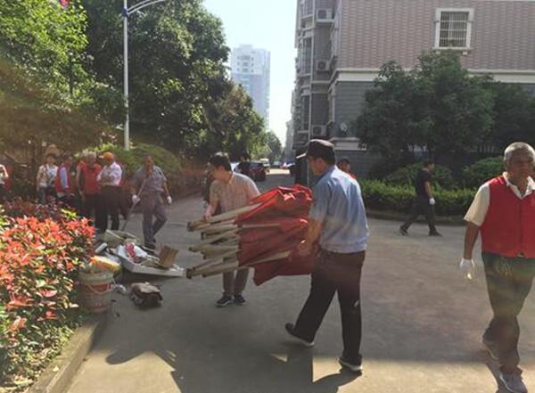 搬离绿化带杂物,劝导住户主动配合整理,并联系交警部门拖离僵尸车。