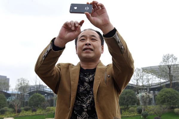看到在他家原址上盖起的梦想小镇新楼,李国强拿出手机拍摄起来。