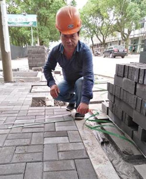 吴友松,章镇镇龙浦新街靓化工程现场施工负责人,图为施工负责人现场检查铺装尺寸。