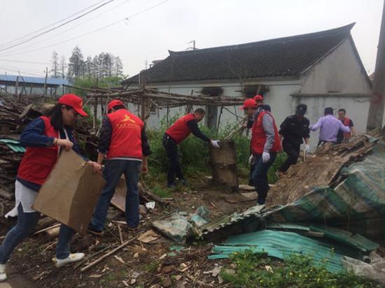 志愿者清理房前屋后乱堆放。