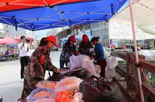 巾帼志愿者服务队帮助桥上摊贩整理搬移。