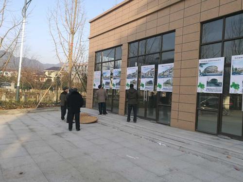 小城镇环境综合整治项目效果图展出,群众正看着展板,展望美好家园。