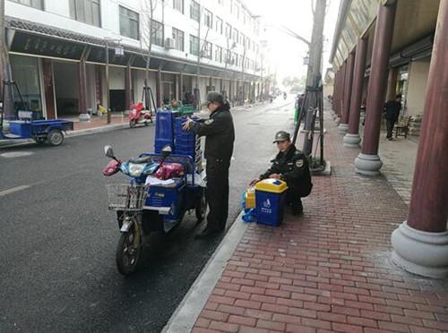 梓桐镇城建办向集镇商户发放垃圾桶,每户的垃圾桶都按编号登记上册。