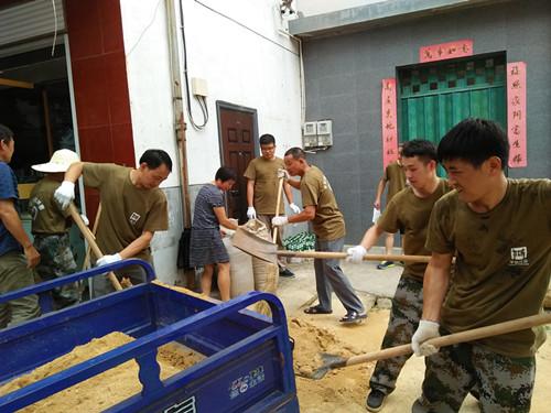 干部群众一家亲,帮助群众清理门前杂物。