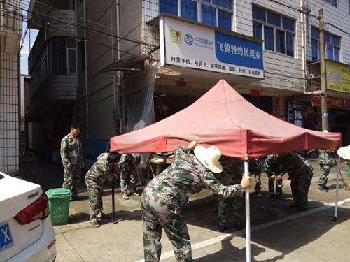 秀峰村党员志愿者清理整治集镇占道经营。