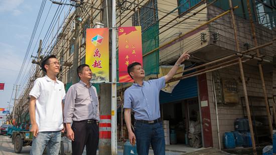 镇工作人员查看沿街立面改造工程进展情况。